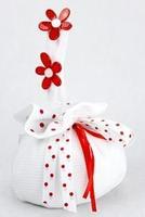 Fagottino in tessuto bianco con due margherite rosse sul manico